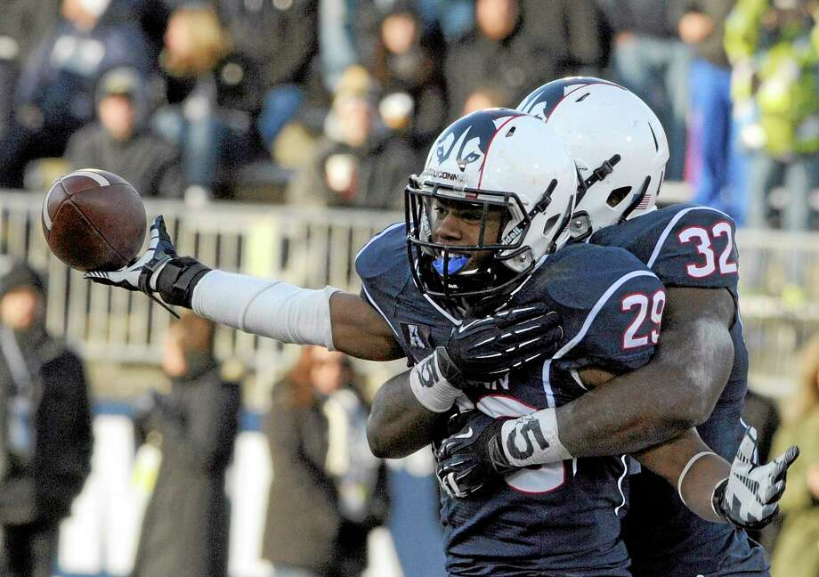 UConn cornerback Taylor Mack (29) and linebacker Jefferson Ashiru (32) celebrate after Mack intercepted a pass during Saturday's game against Rutgers. Photo: Fred Beckham — The Associated Press   / FR153656 AP