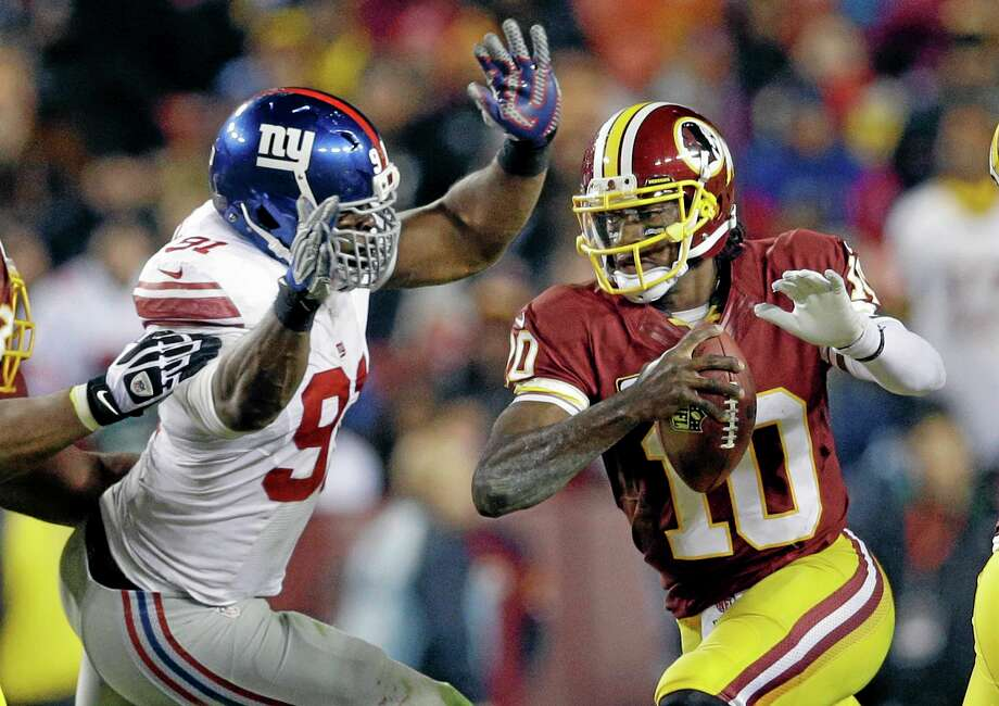 Giants defensive end Justin Tuck, left, tackles Redskins quarterback Robert Griffin III during Sunday's game. Photo: Patrick Semansky — The Associated Press   / AP