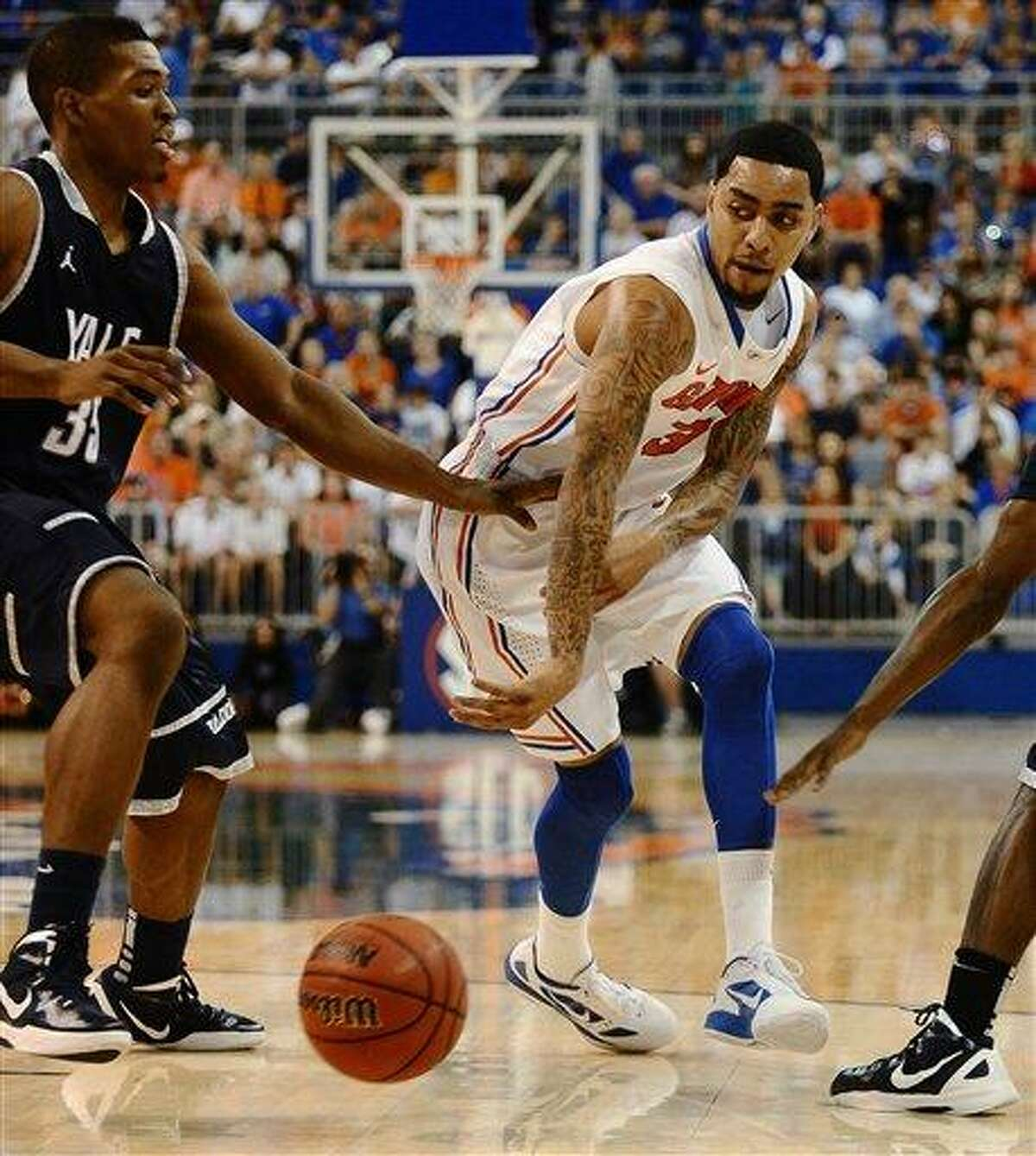 Florida's Mike Rosario (3) passes the ball around Yale's Brandon Sherrod (35) during the first half of an NCAA college basketball game in Gainesville, Fla., Saturday, Dec. 31, 2011. Florida defeated Yale 90-70. (AP Photo/Phil Sandlin)