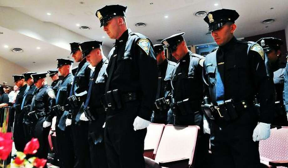 """New police officers about to be sworn in stand during the ceremony at Career High School in New Haven. 26 new officers were sworn in at the ceremony. Peter Casolino/New Haven Register <a href=""""mailto:pcasolino@newhavenregister.com"""">pcasolino@newhavenregister.com</a>"""