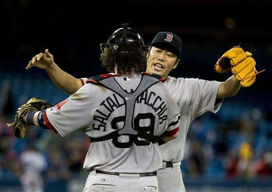 Boston Red Sox pitcher Koji Uehara, back celebrates his teams win with Red Sox catcher Jarrod Saltalamacchia, back, during the eleventh inning of a baseball game in Toronto on Tuesday, August 13, 2013. (AP Photo/The Canadian Press, Nathan Denette) Photo: AP / The Canadian Press