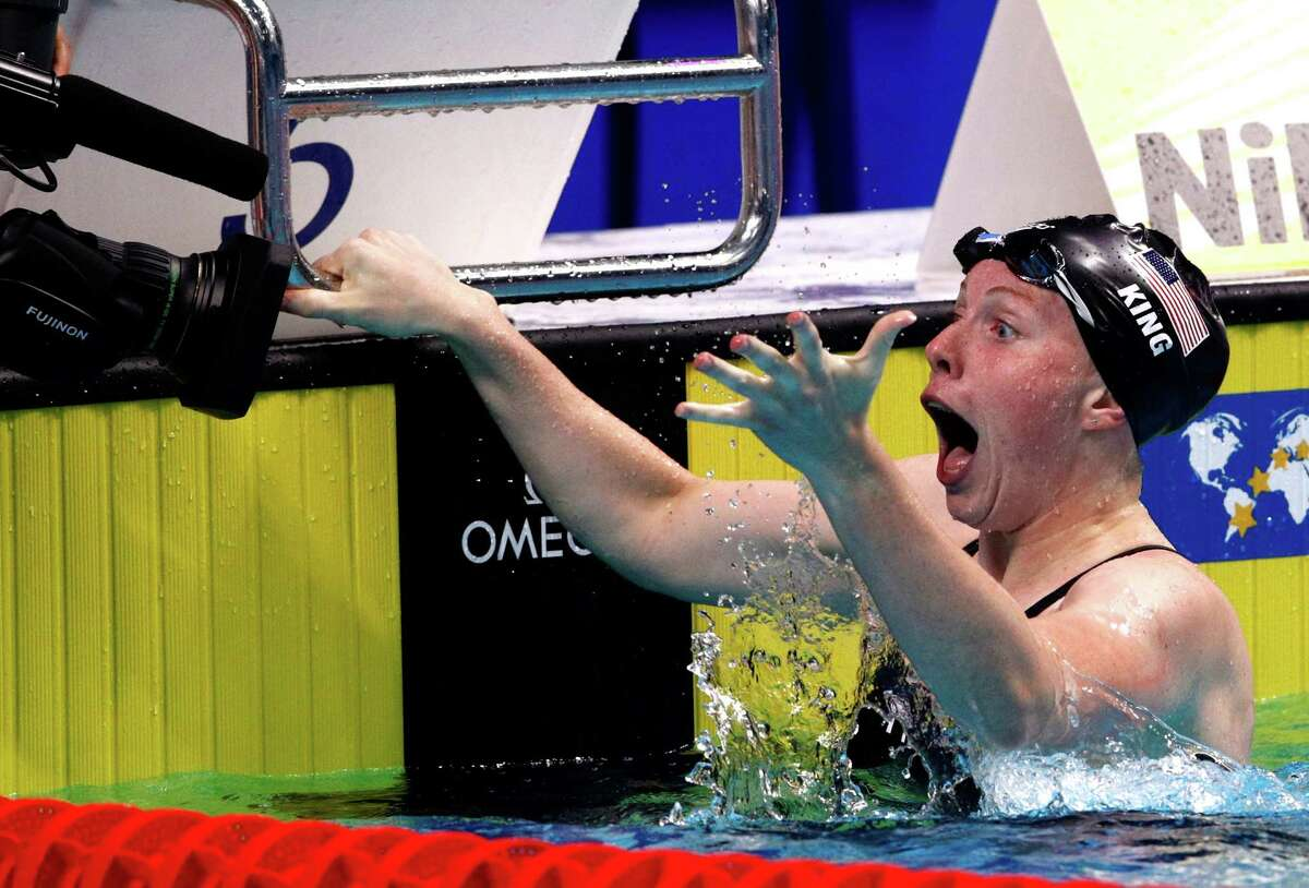 Lilly King rejoices after adding a world title in the 100-meter breaststroke to the Olympic gold she won in the event.