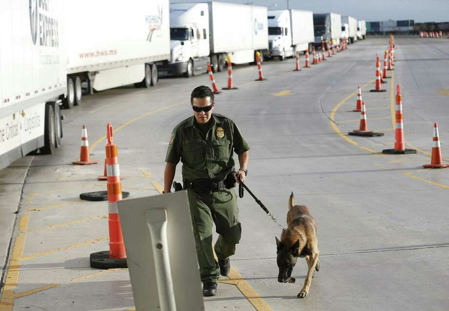 A line of commercial trucks make their way through an inspection station checkpoint as Border Patrol Agent K9 handler officer Garza (no first name used) and his inspection dog make the rounds 27 miles outside Laredo on Tuesday, July 25, 2017. The trailer rig driven by James Matthew Bradley, Jr. that smuggled the ill-fated immigrants may or may not have passed this station. On Tuesday, traffic was heavy yet brisk at the station and agents were out in full force to inspect commercial and personal vehicles heading from Laredo to San Antonio. (Kin Man Hui/San Antonio Express-News) Photo: Kin Man Hui, Staff / San Antonio Express-News / ©2017 San Antonio Express-News