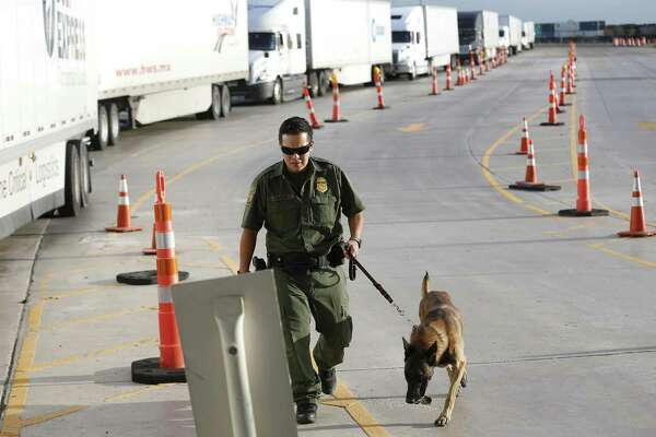 A line of commercial trucks make their way through an inspection station checkpoint as Border Patrol Agent K9 handler officer Garza (no first name used) and his inspection dog make the rounds 27 miles outside Laredo on Tuesday, July 25, 2017. The trailer rig driven by James Matthew Bradley, Jr. that smuggled the ill-fated immigrants may or may not have passed this station. On Tuesday, traffic was heavy yet brisk at the station and agents were out in full force to inspect commercial and personal vehicles heading from Laredo to San Antonio. (Kin Man Hui/San Antonio Express-News)