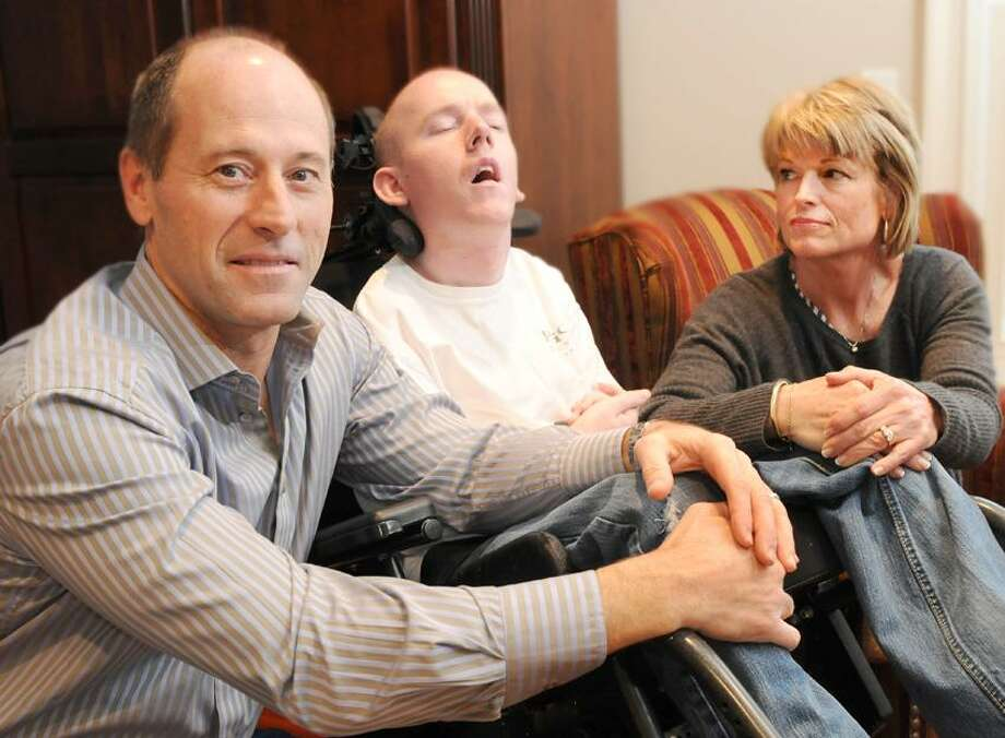 Jack Kelly, his son Brian, 24, and wife Jean at their Branford home. Brian suffers from Adrenoluekodystrophy (ALD). His parents are testifying in a public hearing at the Capitol tomorrow to try and get the screening for this disease covered by insurance. ALD is a disease that if caught early enough, many of the symptoms can be helped. Brian's was caught at age 6, much too late. Tuesday, February 26, 2013. Photo by Peter Hvizdak / New Haven Register Photo: New Haven Register / ©Peter Hvizdak /  New Haven Register