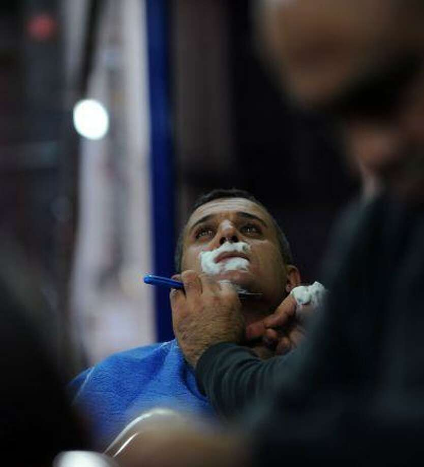A barber shaves a man on January 25, 2013, in Istanbul. Already known the world over for its baths, coffee and sweet Turkish delights, Turkey is on the road to adding another item to its roster of specialities: the moustache. (AFP PHOTO/BULENT KILIC)