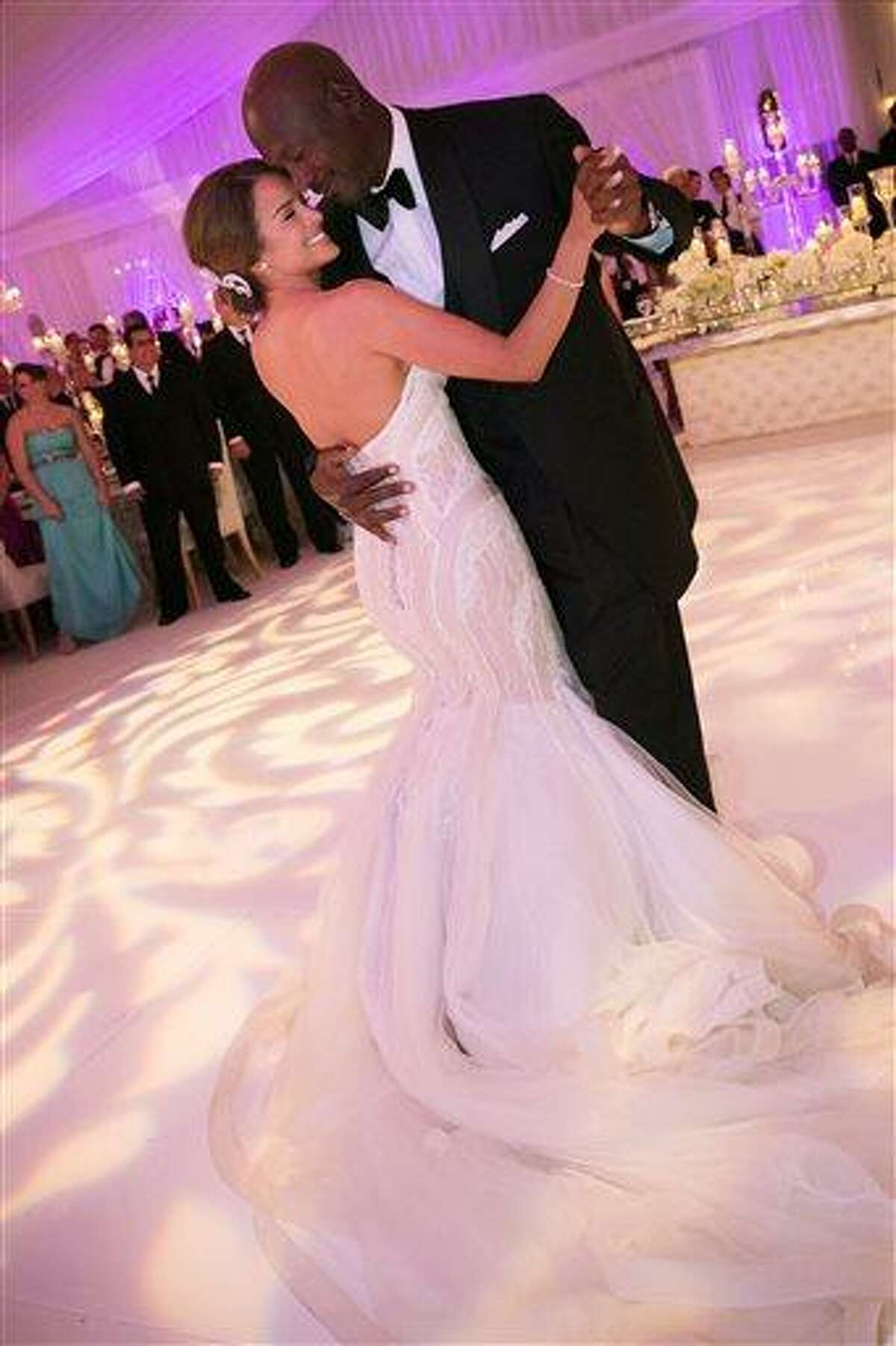 In this Saturday, April 27, 2013, photo provided by JUMP.DC, Charlotte Bobcats owner Michael Jordan dances with his bride Yvette Prieto during their wedding reception at the Bear's Club in Jupiter, Fla. The wedding took place at the Episcopal Church of Bethesda-by-the-Sea with more than 300 guests in attendance, including Tiger Woods, Patrick Ewing and Ahmad Rashad, Jordan's manager Estee Portnoy told The Associated Press Sunday. (AP Photo/JUMP.DC, Joe Buissink)
