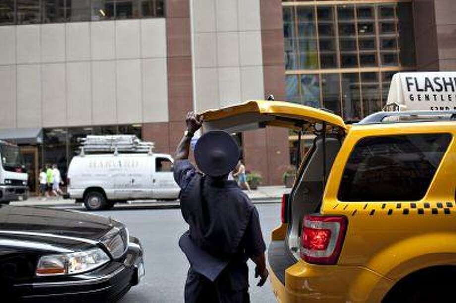 A bellhop closes the trunk of a taxi after loading luggage in New York in 2009. (Bloomberg News photo by Daniel Acker).
