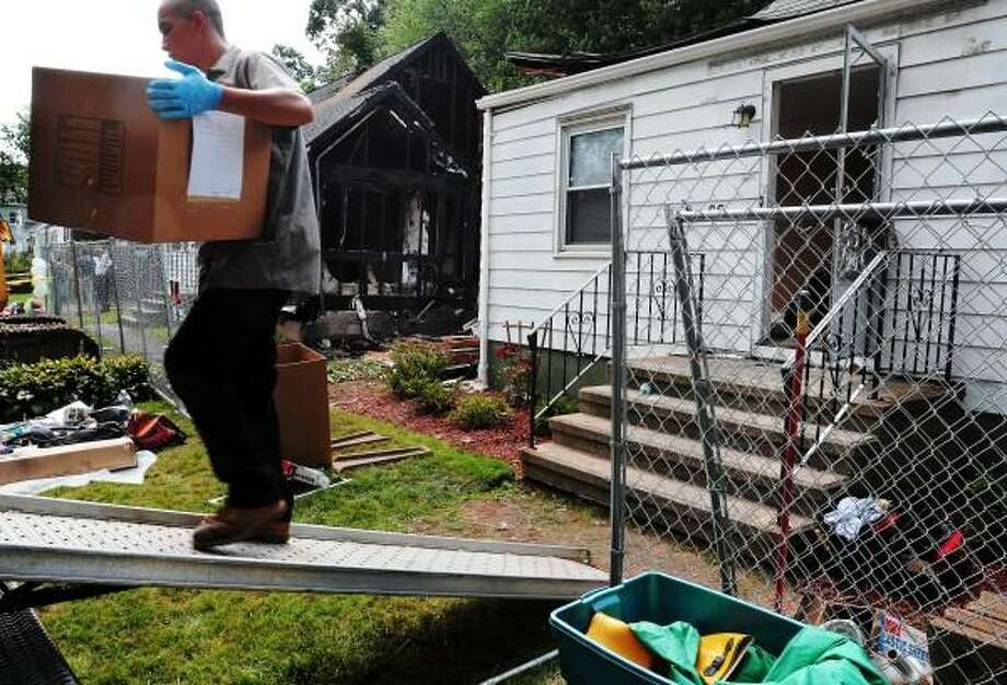 August 12, 2013 East Haven. The site of a plane crash in East Haven, Charter Oak Ave. Movers load belongings from 68 Charter Oak before the house is to be demolished. Mara Lavitt/New Haven Register