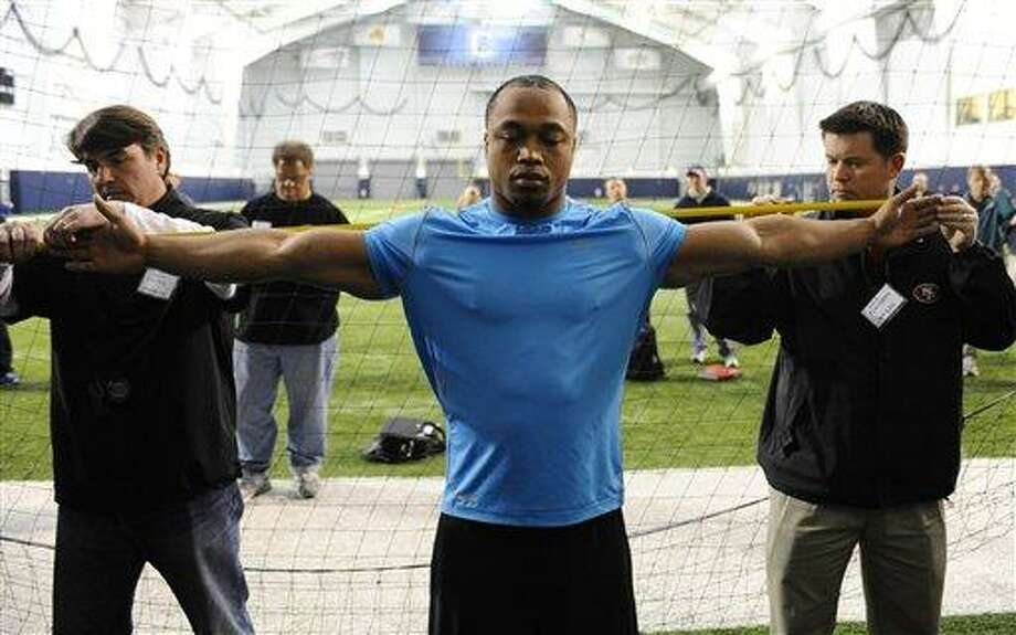 UConn defensive end Trevardo Williams, right, has his arm measured by Panthers scout Robert Haines, left, and 49ers Scout Chip Flanagan, right, during pro day in Storrs, Conn., Wednesday, March 27, 2013.  (AP Photo/Jessica Hill) Photo: ASSOCIATED PRESS / A2013