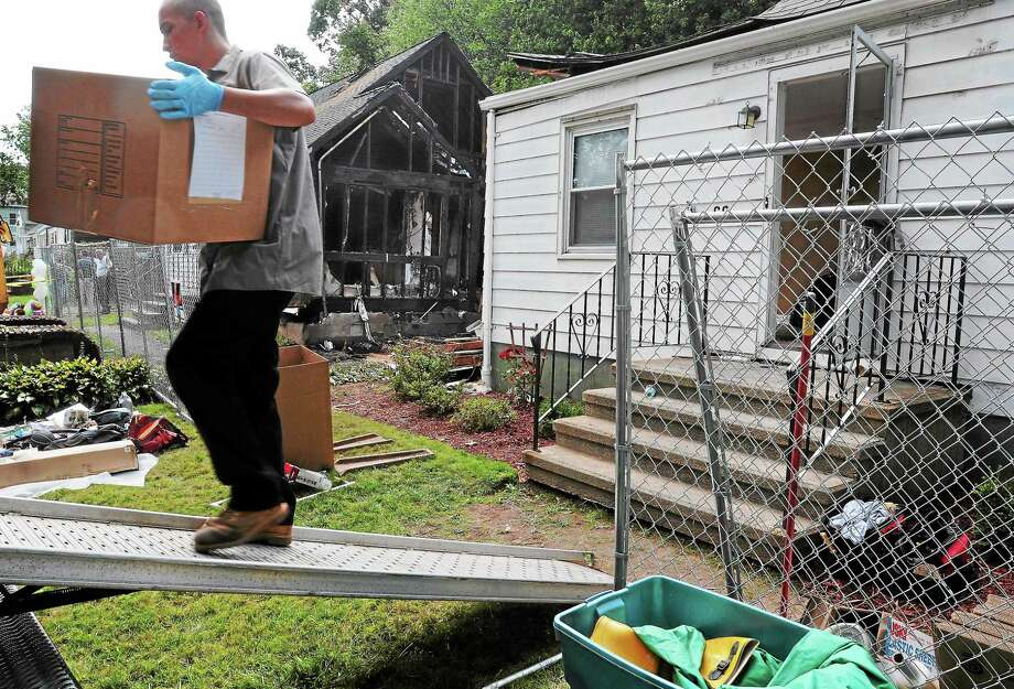 Mara Lavitt — Register August 12, 2013 East Haven. The site of a plane crash in East Haven, Charter Oak Ave. Movers load belongings from 68 Charter Oak before the house is to be demolished. Photo: Journal Register Co.
