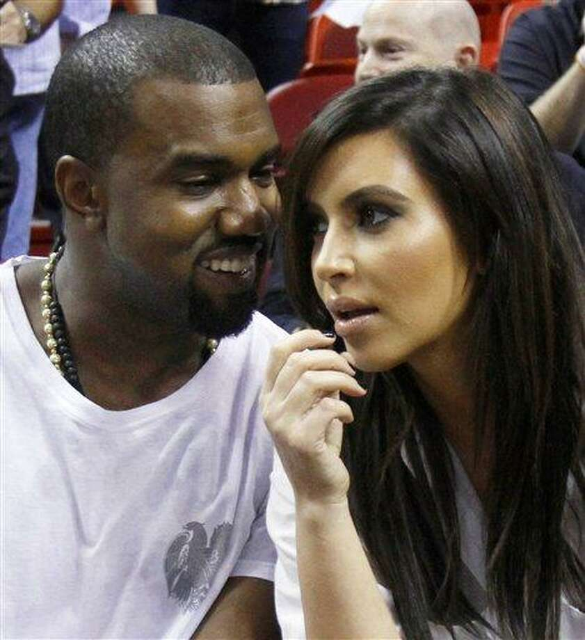 Kanye West, left, talks to his girlfriend Kim Kardashian before an NBA basketball game between the Miami Heat and the New York Knicks in Miami. Authorities say an airline employee is being investigated for allowing West and Kardashian to bypass a security checkpoint at New York's Kennedy Airport. (AP Photo/Alan Diaz, File) Photo: AP / AP