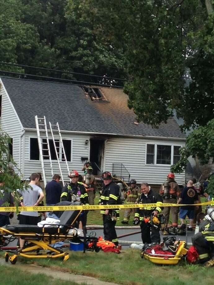 Firefighters cut into rooftop of 64 Charter Oak Ave East Haven  photo by Charlotte Adinolfi