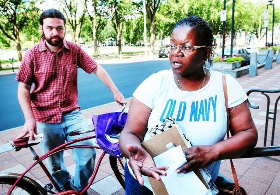 Gregory Williams (left), organizer for Seminarians for a Democratic Society, listens to Barbara Fair (right), founder of My Brother's Keeper, talk about Toad's Place, Ted Nugent and the upcoming Ted Nugent show in front of City Hall in New Haven on 8/4/2013. Arnold Gold - Register