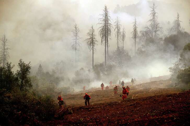 A team of inmate firefighters keep watch on a fire line as they battle the Detwiler Fire on the outskirts of Mariposa on Wednesday, July 19, 2017.