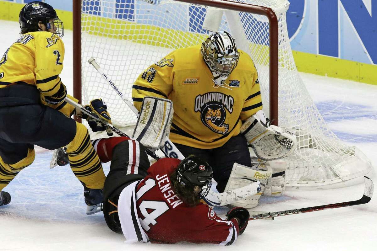 Quinnipiac goalie Eric Hartzell (33) and defenseman Mike Dalhuisen (2) stop a third-period shot by St. Cloud State's Nick Jensen (14) during an NCAA college hockey Frozen Four game in Pittsburgh, Thursday, April 11, 2013. Quinnipaic advances to face Yale for the national championship title on Saturday. (AP Photo/Gene J. Puskar)