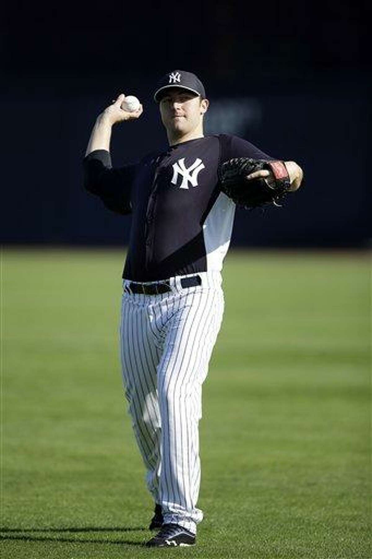 New York Yankees' Phil Hughes pitches during a workout at baseball spring training, Saturday, Feb. 16, 2013, in Tampa, Fla. (AP Photo/Matt Slocum)
