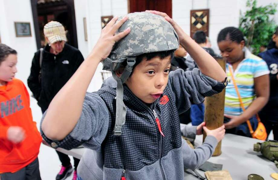 Carrigan Middle School fifth grader Luis Lopez tries on a soldier's helmet during a visit to the West Haven Veterans Museum and Learning Center in West Haven on 4/23/2013.Photo by Arnold Gold/New Haven Register   AG0494B