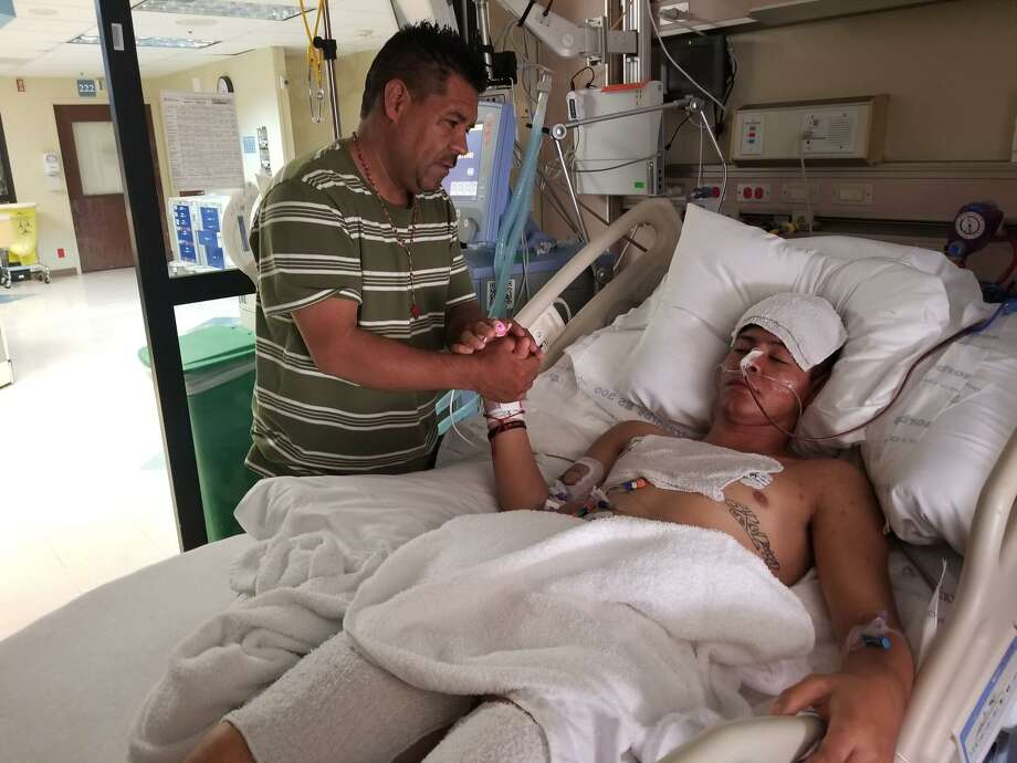 Jose De Jesus Martinez Delgado (left) came from Denver to North Central Baptist Hospital see his 16-year-old son Brandon Rodrigo Martinez Deloera. Brandon is in intensive care with damage to the brain, lungs and liver after spending hours inside a sweltering truck transporting undocumented immigrants Sunday. Photo: Courtesy Of Alex Galvez