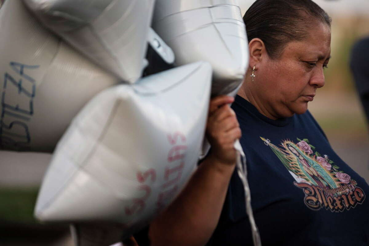 Maria Gonzalez holds balloons with words like fear and sadness written on them with the intention of releasing them to honor the 10 undocumented people who died in San Antonio Sunday morning trying to migrate to the United States. Tuesday, July 25, 2017, in Houston.