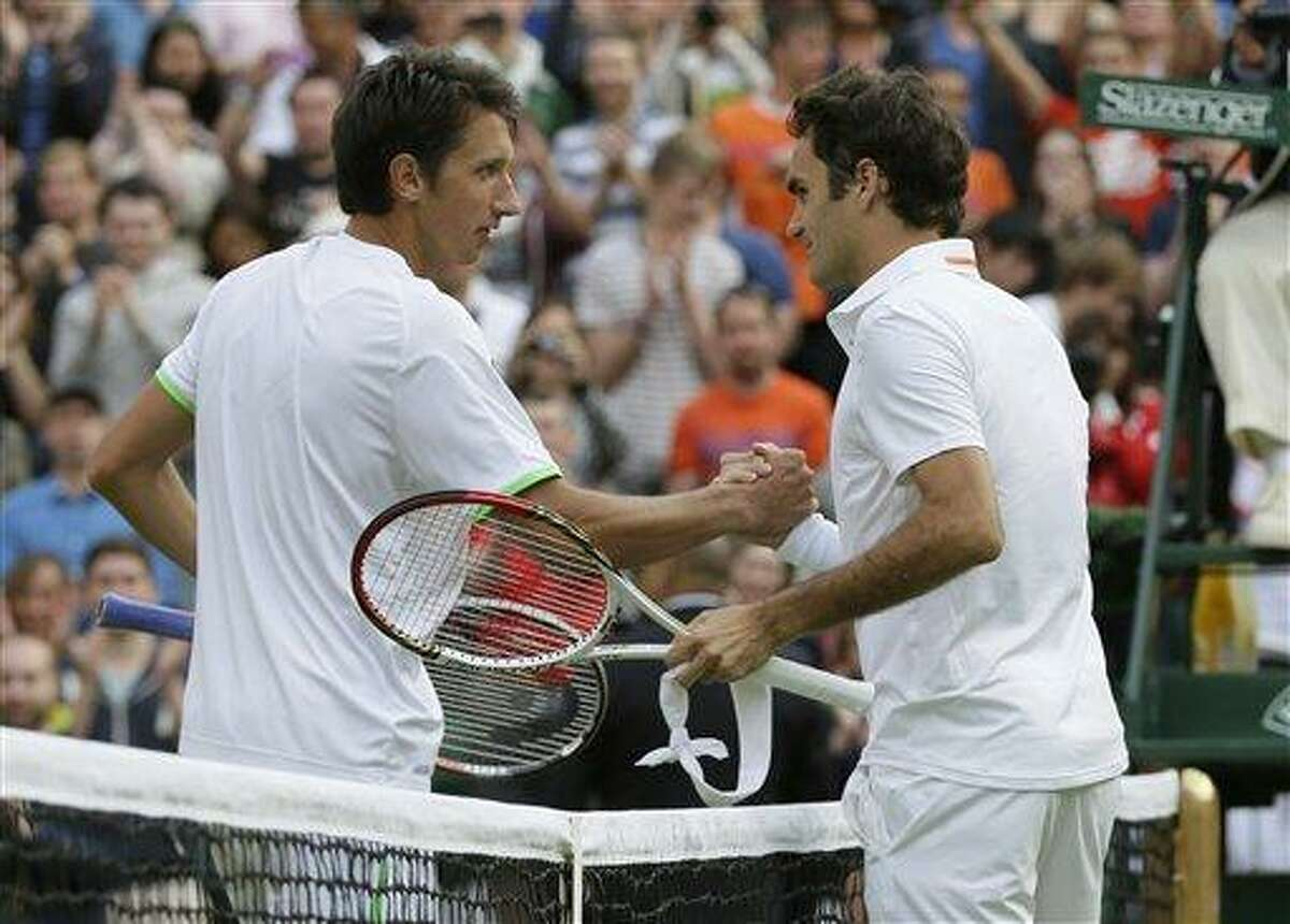Sergiy Stakhovsky of Ukraine, left, shakes hands with Roger Federer of Switzerland after he defeated him in their Men's second round singles match at the All England Lawn Tennis Championships in Wimbledon, London, Wednesday, June 26, 2013. (AP Photo/Alastair Grant)