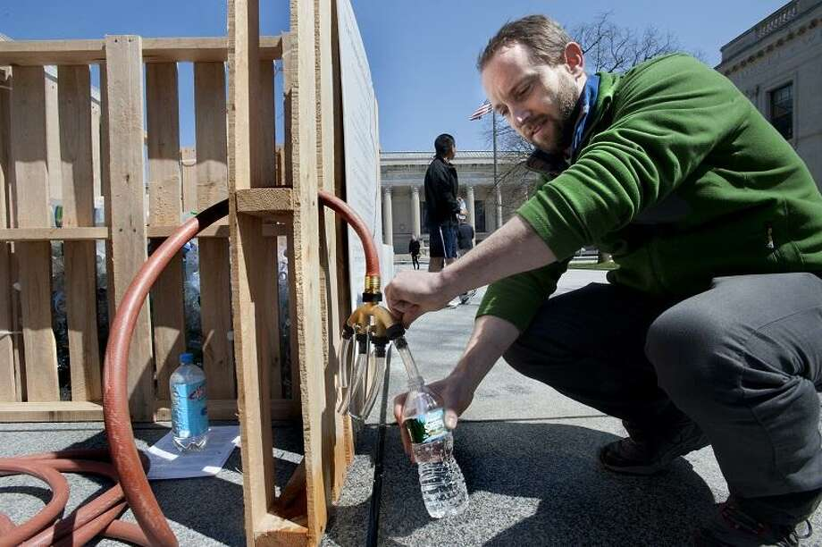 NEW HAVEN-Artist Fritz Horstman, fills a water bottle that will be part of the installation in Beinecke Plaza.  Horstman is Working with the Peabody Museum.    Melanie Stengel/Register