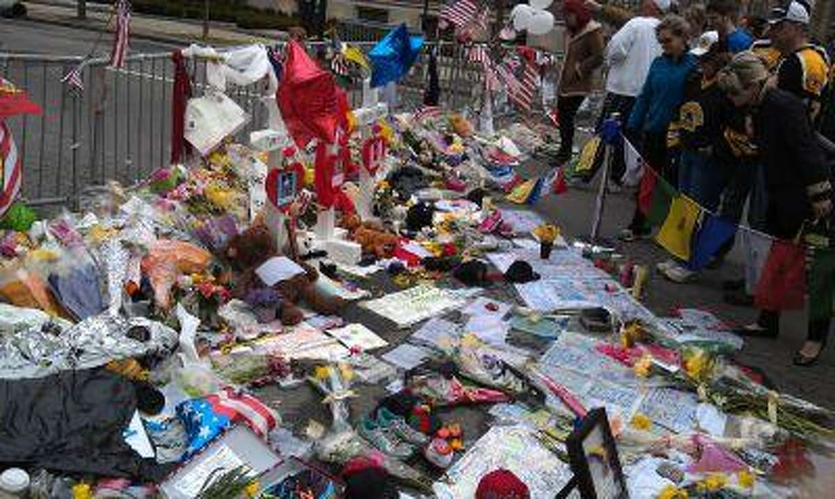 A makeshift memorial for the victims of the Boston Marathon bombing forms Saturday at Copley Square.