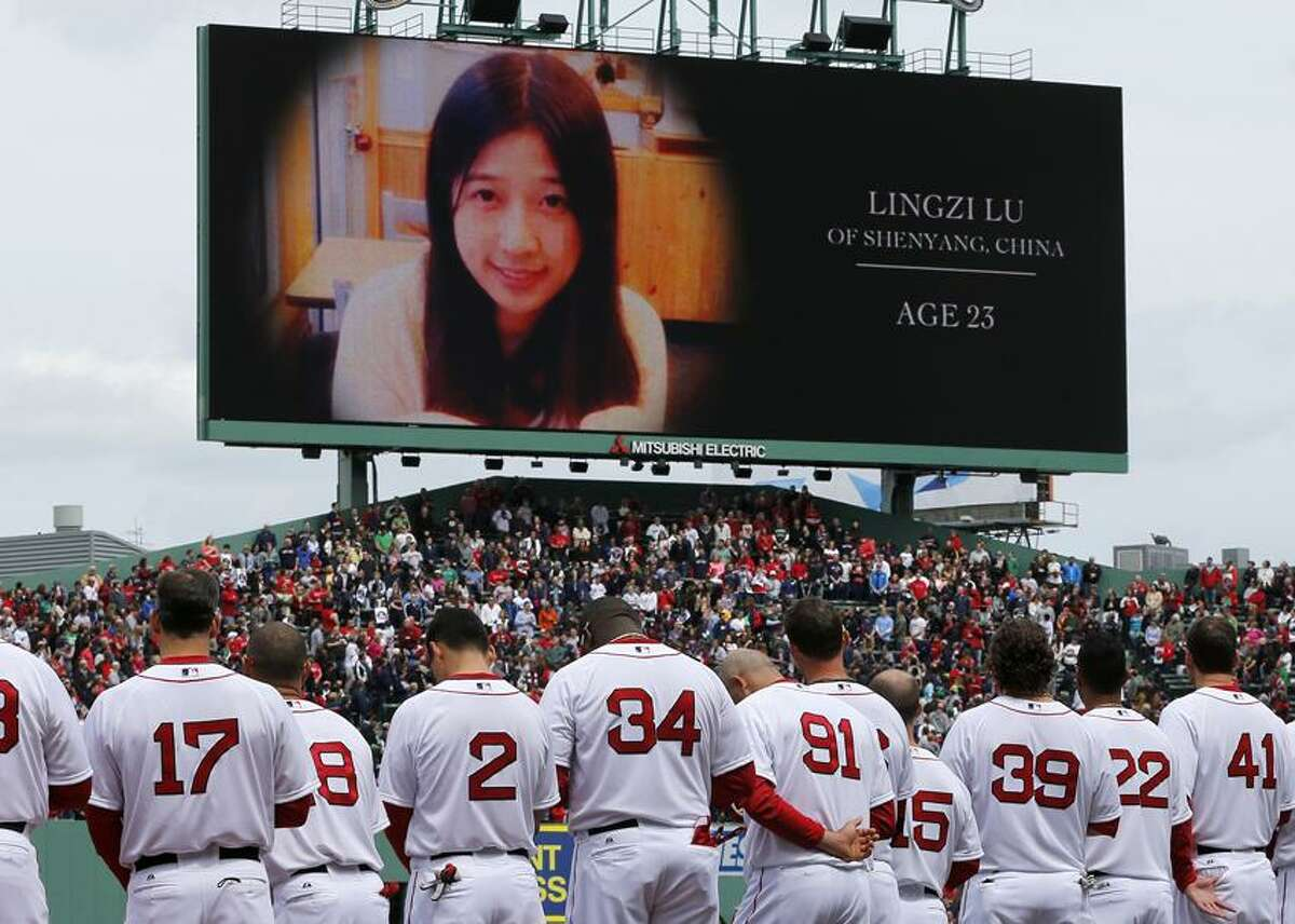 The Boston Red Sox stand during tribute to Boston Marathon bombing victims, including Chinese student Lingzi Lu, before a baseball game against the Kansas City Royals in Boston, Saturday, April 20, 2013. (AP Photo/Michael Dwyer)