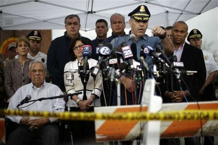 State Police Col. Timothy Alben, at podium, accompanied by Massachusetts Governor Deval Patrick, second right, and Boston Mayor Thomas Menino, lower left, gestures during a news conference regarding manhunt for Boston Marathon bombings suspect Dzhokar Tsarnaev, Friday, April 19, 2013, in Watertown, Mass. Alben said that he believed  the19-year-old college student Tsarnaev was still in Massachusetts because of his ties to the area. But authorities lifted the stay-indoors warning for people in the Boston area, and the transit system started running again by evening. (AP Photo/Matt Rourke) Photo: AP / AP