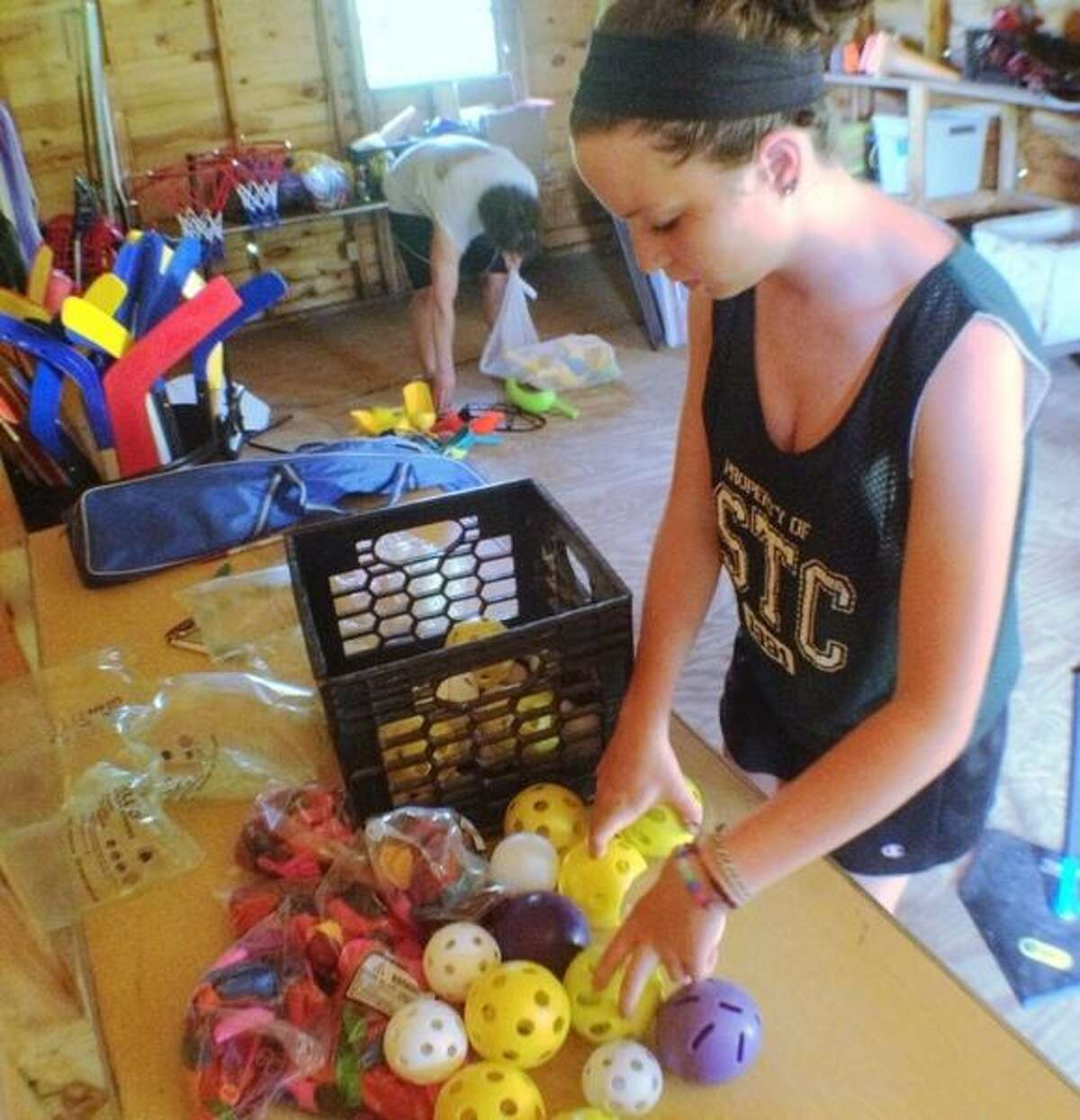 JOHN HAEGER @ONEIDAPHOTO ON TWITTER/ONEIDA DAILY DISPATCH Kelli Vachon works to inventory sports equipment at Madison County Childrens Camp Camp Lookout on Monday, June 24, 2013.