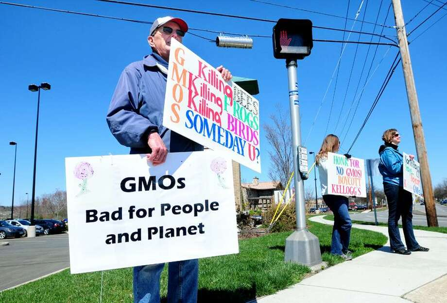 Left to right, Herb Milek of Branford, Cheryl Coveyduck of Branford and Tami Reagor of Wallingford protest the use of GMOs, Genetically Modified Organisms, in food on Universal Drive in North Haven on 4/21/2013.Photo by Arnold Gold/New Haven Register  AG0493C