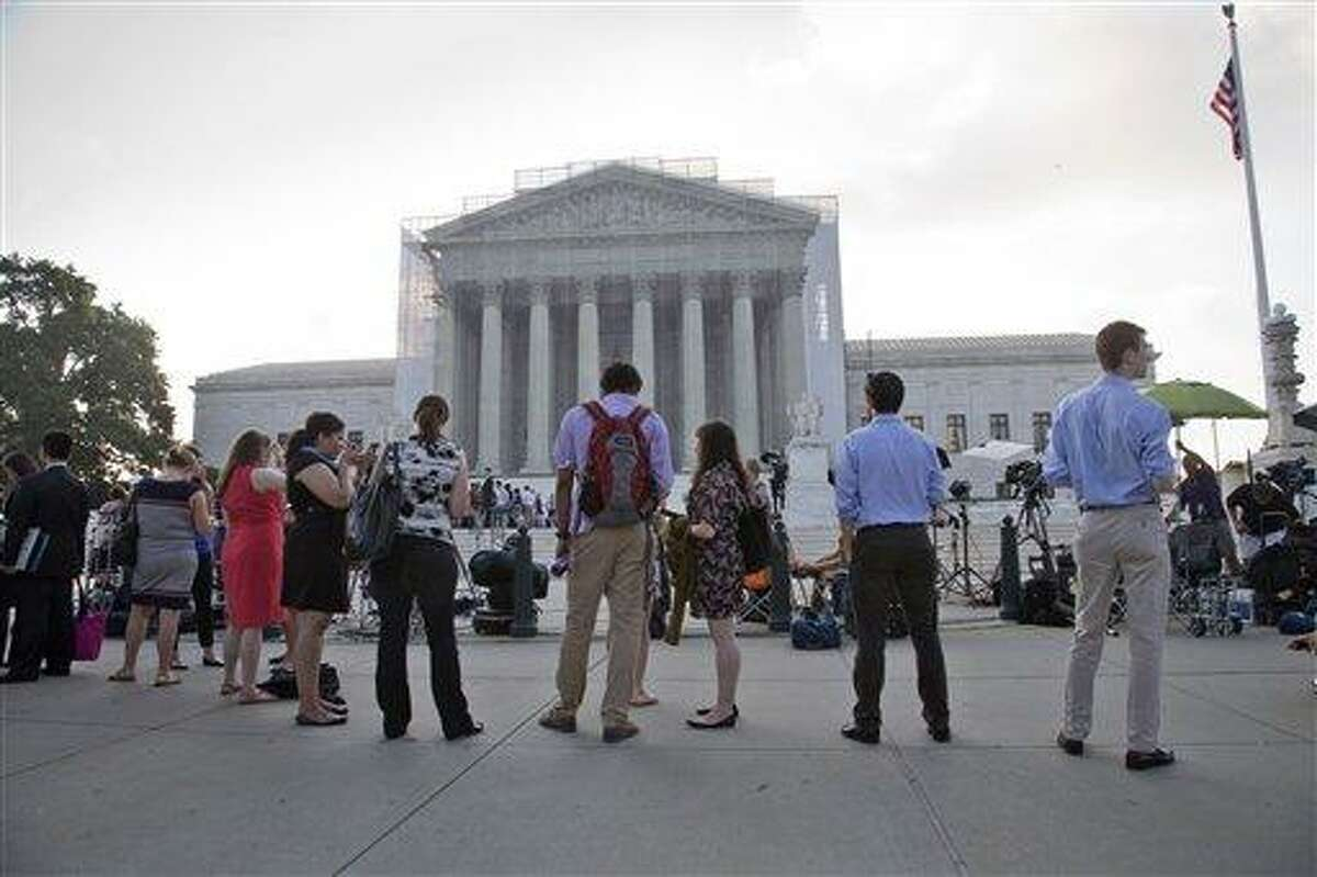 FILE - This June 24, 2013 file photo shows people waiting outside the Supreme Court in Washington as key decisions are expected to be announced. The Supreme Court said Tuesday that a key provision of the landmark Voting Rights Act cannot be enforced until Congress comes up with a new way of determining which states and localities require close federal monitoring of elections. (AP Photo/J. Scott Applewhite, File)