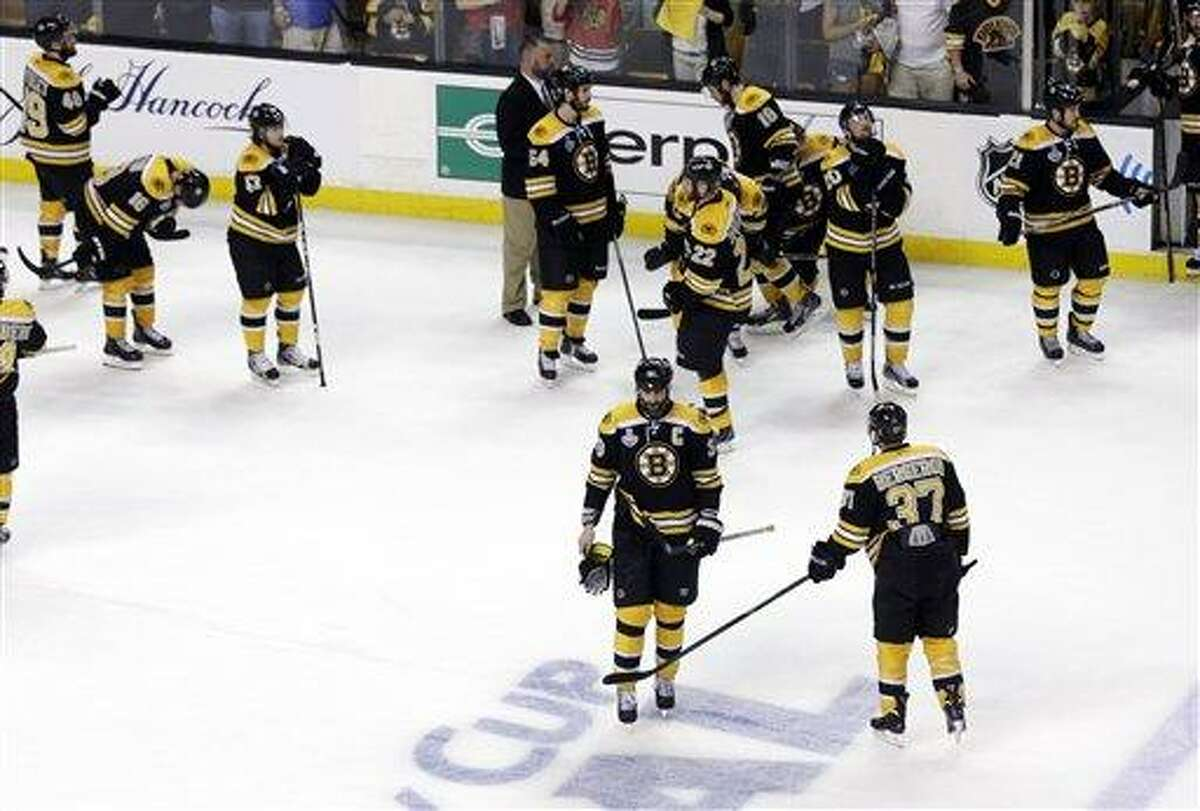 Boston Bruins center Patrice Bergeron (37) taps defenseman Zdeno Chara (33), of Slovakia, as the team stands on the ice while the Chicago Blackhawks celebrate their 3-2 win in Game 6 of the NHL hockey Stanley Cup Finals, Monday, June 24, 2013, in Boston. (AP Photo/Charles Krupa)