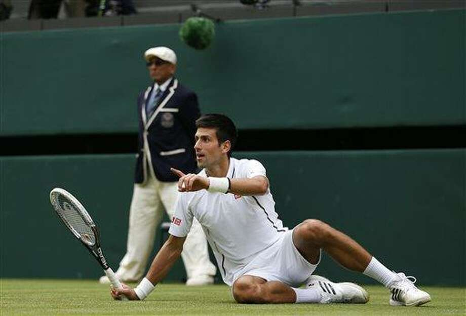 Novak Djokovic of Serbia gestures after slipping against Florian Mayer of Germany in their Men's first round singles match at the All England Lawn Tennis Championships in Wimbledon, London,  Tuesday, June 25, 2013. (AP Photo/Sang Tan) Photo: AP / AP