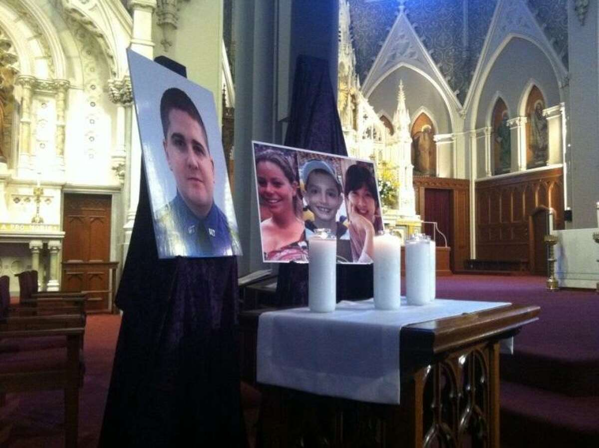 Inside Cathedral of the Holy Cross are photos on an altar of the victims who died in the Boston Marathon bombings. Photo by Jennifer Swift