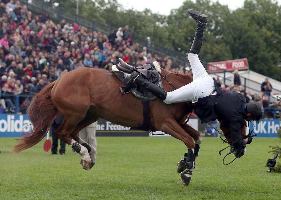 Britain's Joao Charlesworth riding Hartleymanor Venus has trouble as they come down off the Derby Bank during the Hickstead Derby at the The All England Jumping Course, Hickstead, Engalnd, Sunday June 23, 2013. The horse and rider were shaken by the event but seemed unhurt. (AP Photo / Steve Parsons, PA) Photo: ASSOCIATED PRESS / AP2013