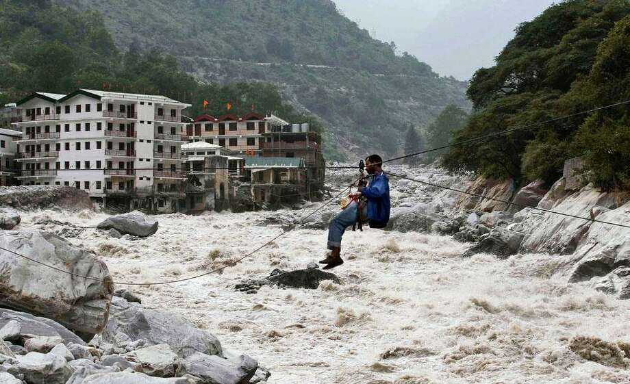 An Indian man crosses over a swollen river with the help of a rope in Govindghat, India, Sunday, June 23, 2013. Bad weather hampered efforts Sunday to evacuate thousands of people stranded in the northern India state of Uttarakhand, where at least 1,000 people have died in monsoon flooding and landslides, army officials said. (AP Photo/Rafiq Maqbool) Photo: ASSOCIATED PRESS / AP2013