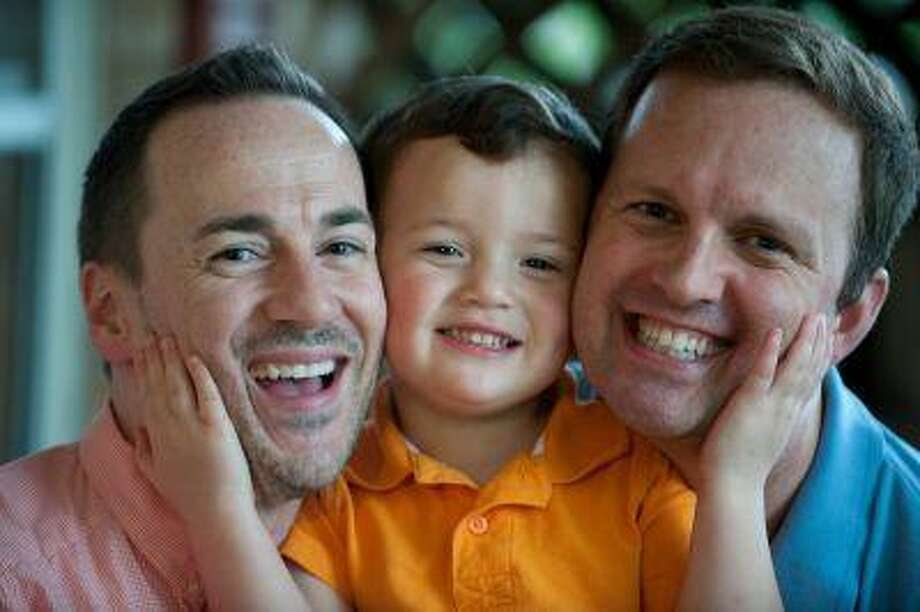 Brad Benton, center, and Brad Letson play with their adopted son Kyler Benton-Letson at their home in Silver Spring, Md. (For The Washington Post/Mary F. Calvert)