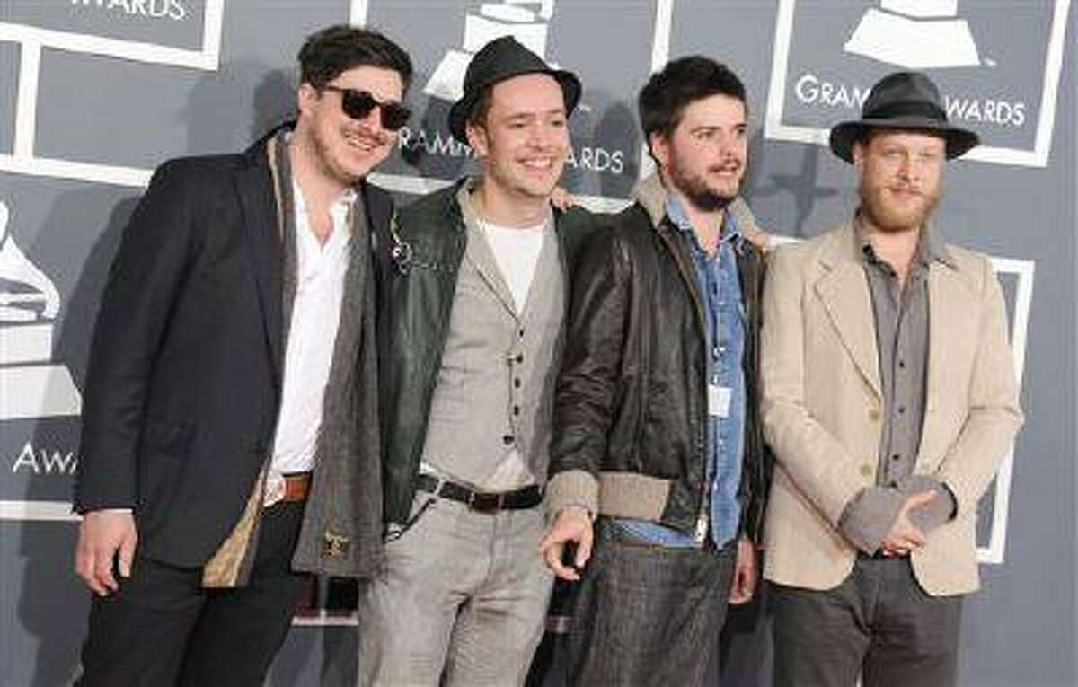 This Feb. 10, 2013 file photo shows, from left, Marcus Mumford, Ben Lovett, Country Winston and Ted Dwane, of Mumford & Sons, at the 55th annual Grammy Awards in Los Angeles. The Grammy-winning band announced Monday, June 24, rescheduled dates in Dallas, Woodlands, New Orleans and Kansas City. The upcoming shows will include bassist Ted Dwane, who received treatment for a blood clot on his brain two weeks ago. (Jordan Strauss/Invision/AP/file)