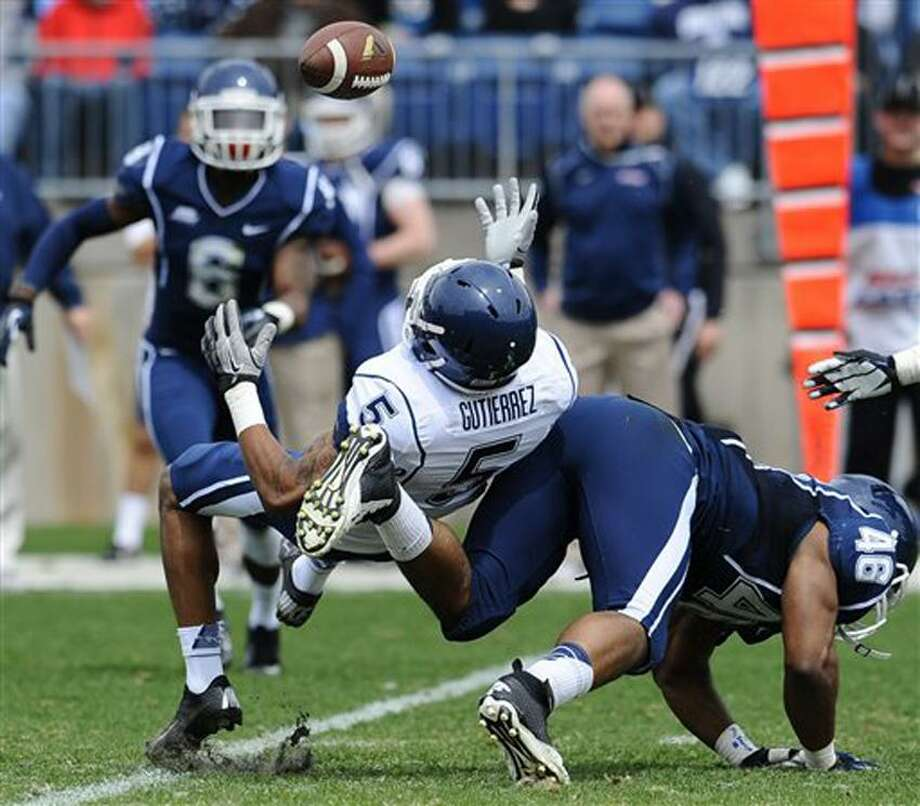 Connecticut's Ricky Gutierrez, left, is upended by Marquise Vann during the UConn's Blue-White spring NCAA college football game at Rentschler Field in East Hartford, Conn., Saturday, April 20, 2013. (AP Photo/Jessica Hill) Photo: AP / FR125654 AP