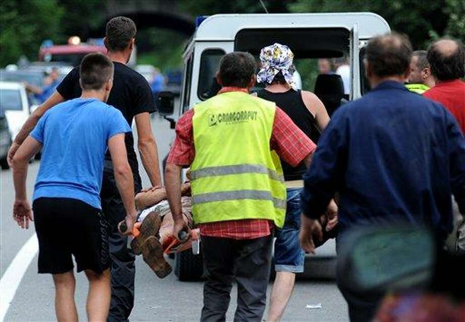 People carry injured man after a bus crash near Kolasin some 30 kilometers (18 miles) north of the capital Podgorica, Montenegro, Sunday, June 23, 2013. At least 13 people were killed and 32 were injured when a bus carrying Romanian tourists swayed off a bridge and plunged into a deep ravine in central Montenegro on Sunday, police said. The winding road that leads from Serbia in the north through the Moraca canyon and then to the seacoast is notorious for traffic accidents because it is narrow and slippery in wet weather conditions, and is considered one of the most dangerous to drive in the region. (AP Photo/Risto Bozovic) Photo: AP / AP