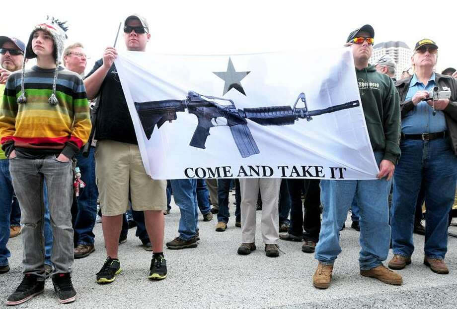 Brian Stevens (left) and Todd Nihill (right) of Seymour hold a banner of an AR-15 semi-automatic rifle during a rally supporting the repeal of Connecticut's new gun laws in front of the Capitol in Hartford on 4/20/2013.Photo by Arnold Gold/New Haven Register   AG0493B