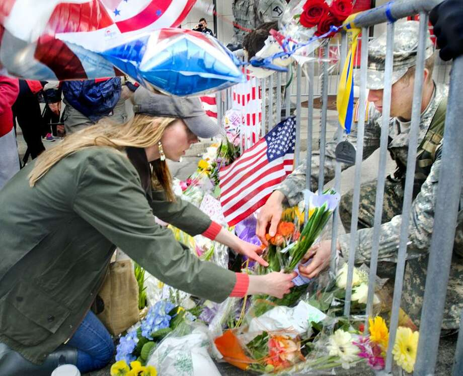 Boston-National Guard Lt. Garrett Robinson, of Kittery, Maine (R)  helps a woman who did not wish to be identified place floweres at a memorial on Boylston Street.  Melanie Stengel/Register