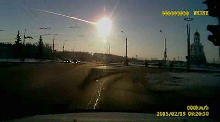 In this frame grab made from dashboard camera video, a meteor streaks through the sky over Chelyabinsk, about 1500 kilometers (930 miles) east of Moscow, Friday, Feb. 15, 2013. With a blinding flash and a booming shock wave, the meteor blazed across the western Siberian sky Friday and exploded with the force of 20 atomic bombs, injuring more than 1,000 people as it blasted out windows and spread panic in a city of 1 million. (AP Photo/AP Video) Photo: AP / AP2013