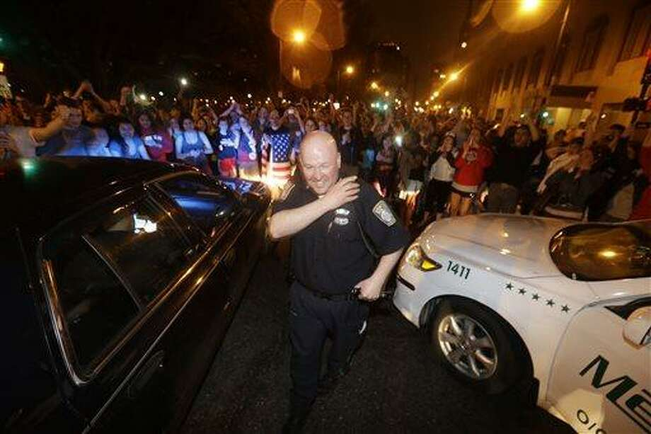 A police officer reacts to news of the arrest of one of the Boston Marathon bombing suspects, Friday, April 19, 2013, in Boston. Boston Marathon bombing suspect Dzhokhar Tsarnaev was captured in Watertown, Mass. The 19-year-old college student wanted in the bombings was taken into custody Friday evening after a manhunt that left the city virtually paralyzed and his older brother and accomplice dead. (AP Photo/Julio Cortez) Photo: AP / AP