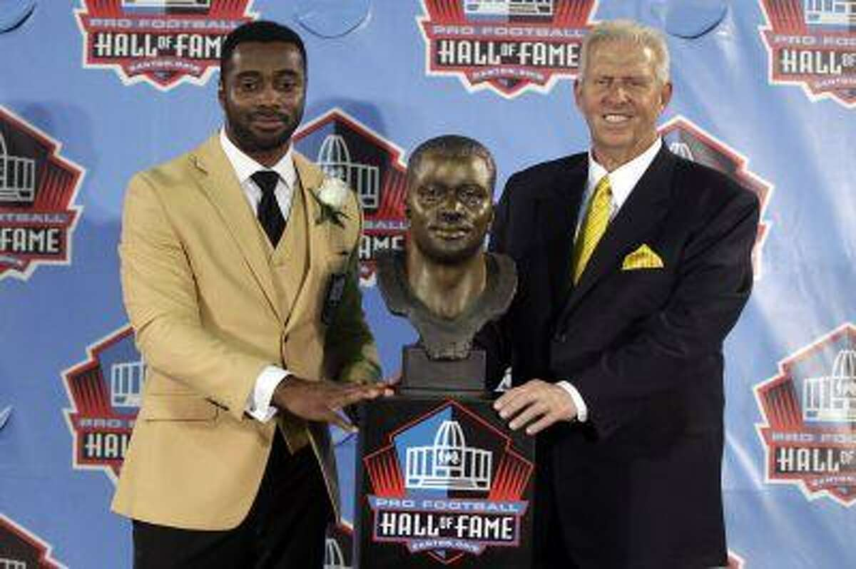 Curtis Martin and former head coach Bill Parcells pose for a photograph with Martin's bust at the 2012 Hall of Fame Enshrinee Ceremony at Fawcett Stadium in Canton, Ohio on August 4, 2012.