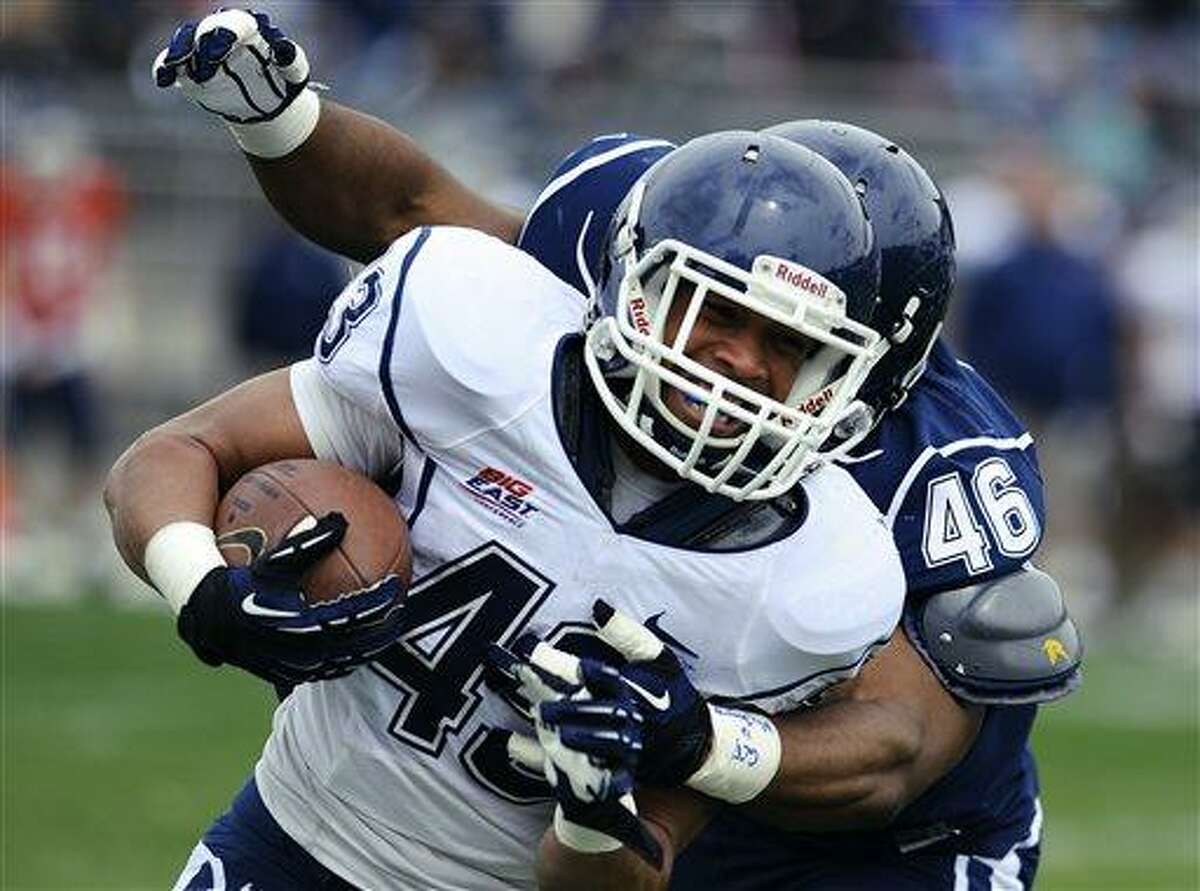 Connecticut's Lyle McCombs carries the ball as Marquise Vann, right, defends during UConn's Blue-White spring NCAA college football game at Rentschler Field in East Hartford, Conn., Saturday, April 20, 2013. (AP Photo/Jessica Hill)