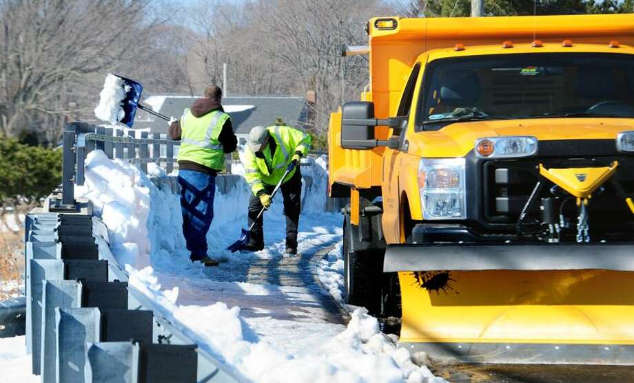 Milford Public Works employees shovel packed snow and ice from a walkway on a bridge on Gulf St. in Milford on 2/14/2013.Photo  by Arnold Gold/New Haven Register   AG0483B
