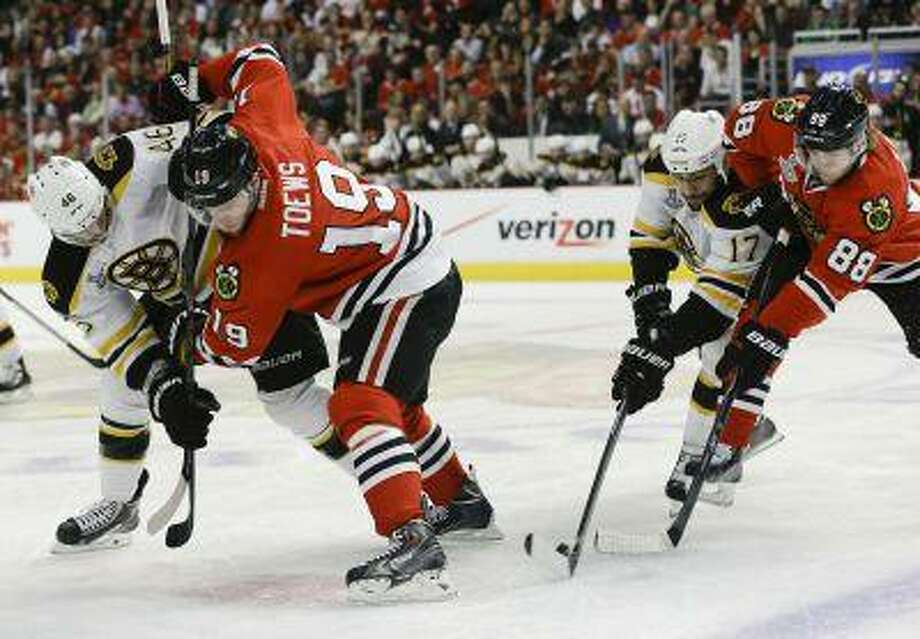 Boston Bruins left wing Milan Lucic (17) and Chicago Blackhawks right wing Patrick Kane (88) battle to control the face off from Boston Bruins center David Krejci (46) and Chicago Blackhawks center Jonathan Toews (19) in the first period during Game 5 of the NHL hockey Stanley Cup Finals, Saturday, June 22, 2013, in Chicago. Photo: AP / AP