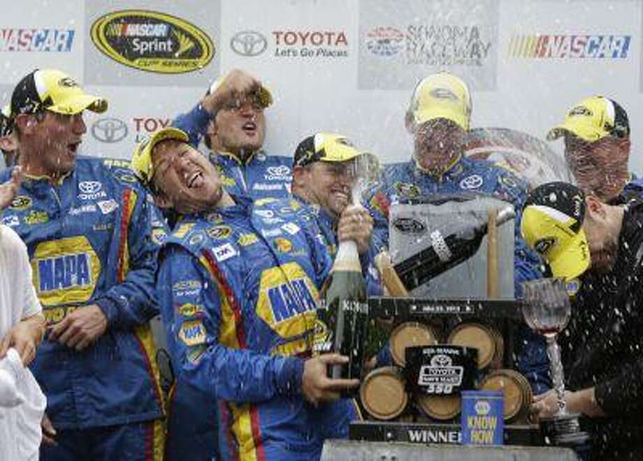 Martin Truex Jr., second from left, sprays his team after winning the NASCAR Sprint Cup series auto race on Sunday, June 23, 2013, in Sonoma, Calif. Photo: AP / AP